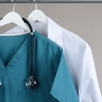 Closeup of a doctor's scrubs with stethoscope and lab coat on hangers against a neutral background.